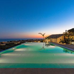 Foto di una grande piscina a sfioro infinito stile marino rettangolare dietro casa