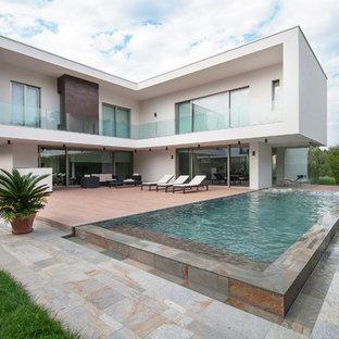 Idee per un'ampia piscina monocorsia design rettangolare dietro casa con pavimentazioni in pietra naturale