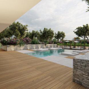 Modelo de piscina alargada, actual, grande, a medida, en patio trasero, con losas de hormigón