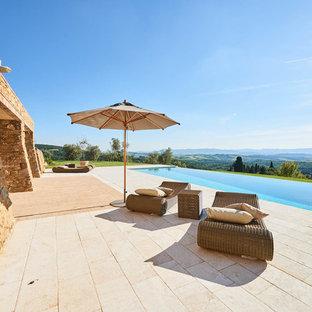 Immagine di una piscina a sfioro infinito mediterranea rettangolare dietro casa