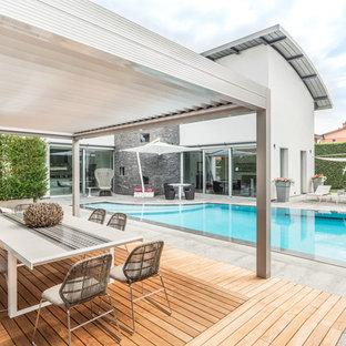 Immagine di una piscina minimal personalizzata dietro casa con pavimentazioni in cemento