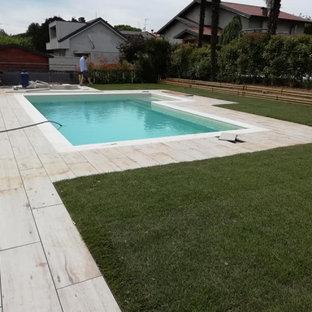 Imagen de piscina de tamaño medio, en forma de L, en patio trasero, con privacidad y suelo de baldosas