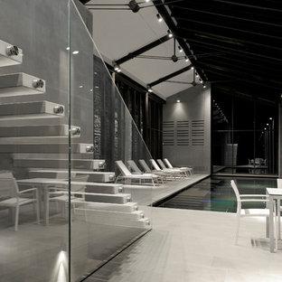 Diseño de piscina infinita, contemporánea, de tamaño medio, interior y rectangular, con adoquines de piedra natural