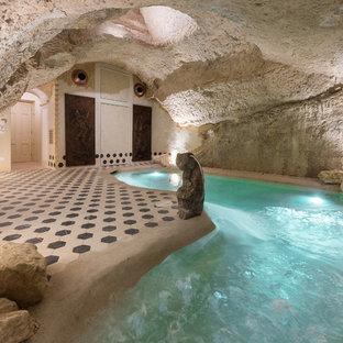 Foto de piscina ecléctica, pequeña, interior y a medida, con adoquines de piedra natural