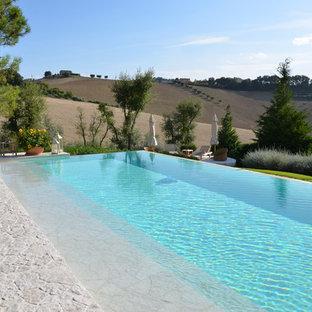 Immagine di una piscina a sfioro infinito in campagna rettangolare con pavimentazioni in pietra naturale