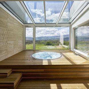 Esempio di una piscina minimal rotonda in cortile con una vasca idromassaggio e pedane