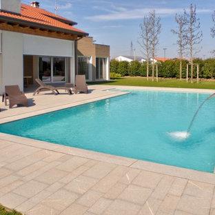 Ejemplo de piscina con fuente infinita, actual, grande, rectangular, en patio delantero, con adoquines de piedra natural