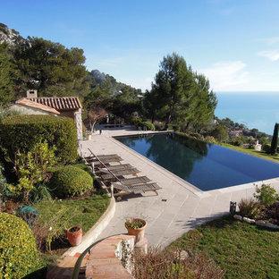 Ispirazione per una grande piscina a sfioro infinito mediterranea rettangolare dietro casa con piastrelle e una dépendance a bordo piscina