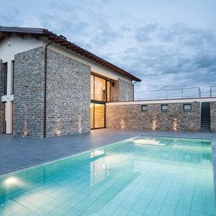 Esempio di una piscina country rettangolare dietro casa