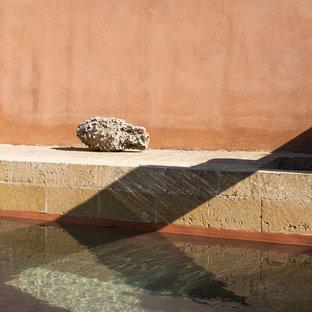 Imagen de piscina infinita, mediterránea, grande, rectangular, en patio, con adoquines de piedra natural