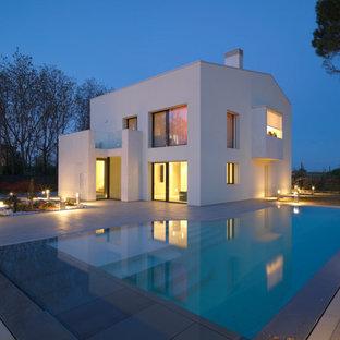 Modelo de piscinas y jacuzzis infinitos, contemporáneos, de tamaño medio, en forma de L, en patio delantero, con adoquines de piedra natural