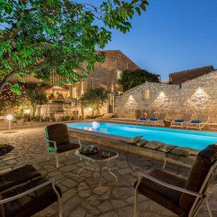 Esempio di una piscina mediterranea rettangolare dietro casa con pavimentazioni in pietra naturale