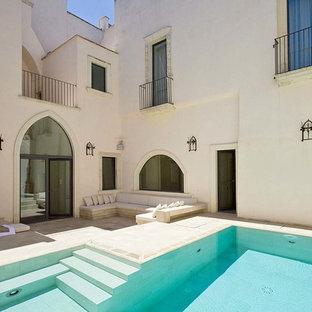 Ejemplo de piscinas y jacuzzis infinitos, mediterráneos, de tamaño medio, en forma de L, en patio lateral, con adoquines de piedra natural