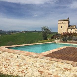 Imagen de casa de la piscina y piscina elevada, de estilo de casa de campo, pequeña, en forma de L, en patio delantero, con adoquines de ladrillo