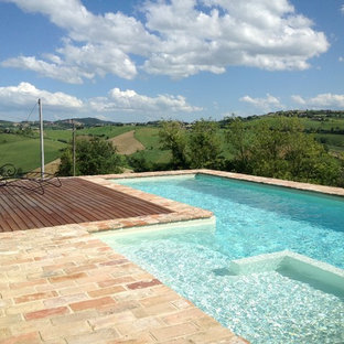 Small country l-shaped aboveground pool in Other with a pool house and natural stone pavers.
