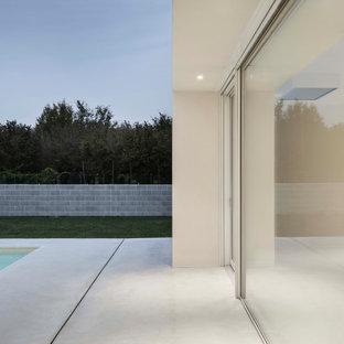 Imagen de piscina actual, grande, rectangular, en patio, con privacidad y adoquines de hormigón
