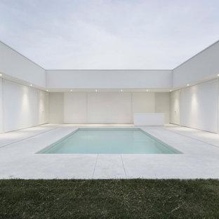 Ejemplo de piscina contemporánea, grande, rectangular, en patio, con privacidad y adoquines de hormigón