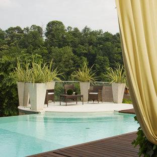 Ispirazione per una grande piscina a sfioro infinito mediterranea personalizzata dietro casa con pedane