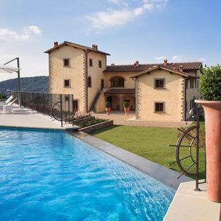 Ispirazione per una piscina a sfioro infinito mediterranea personalizzata dietro casa con pedane