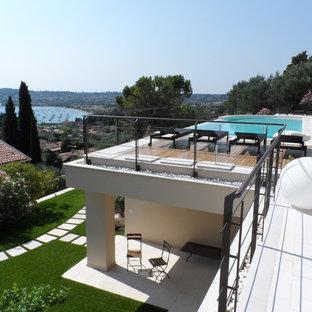 Ispirazione per una piscina a sfioro infinito design personalizzata sul tetto con piastrelle