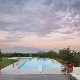 Idee per una piscina monocorsia country personalizzata dietro casa con piastrelle