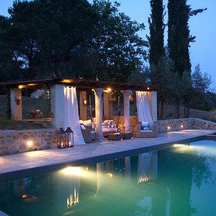 Ispirazione per un'ampia piscina a sfioro infinito stile rurale rettangolare dietro casa con una dépendance a bordo piscina e pavimentazioni in pietra naturale