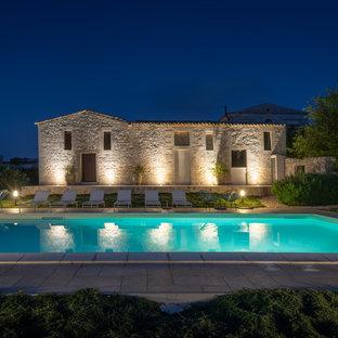 Esempio di una grande piscina monocorsia mediterranea rettangolare dietro casa con pavimentazioni in cemento