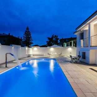 Foto de piscina con fuente contemporánea, en patio lateral, con adoquines de piedra natural