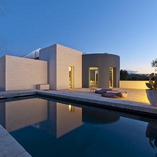 Immagine di una piscina design rettangolare di medie dimensioni e dietro casa con pavimentazioni in pietra naturale
