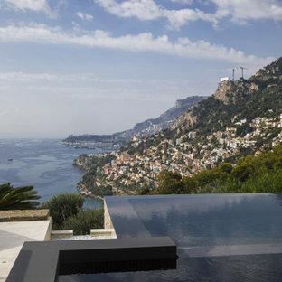 Imagen de piscina infinita, moderna, con adoquines de piedra natural