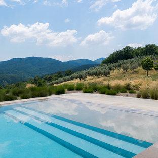 Ejemplo de piscina infinita, rústica, grande, rectangular, en patio trasero, con adoquines de piedra natural