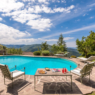 Inspiration for a mid-sized country backyard kidney-shaped pool in Florence with natural stone pavers.