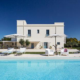Ispirazione per una grande piscina monocorsia mediterranea rettangolare dietro casa con lastre di cemento