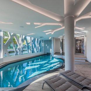 Foto di una piscina coperta design personalizzata con pedane