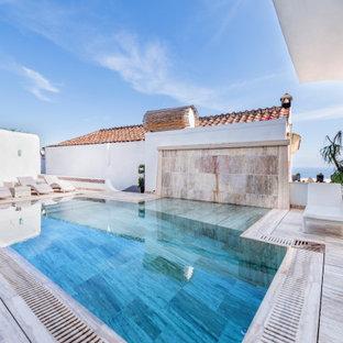 Diseño de piscina infinita, actual, grande, a medida, en patio, con privacidad y adoquines de piedra natural