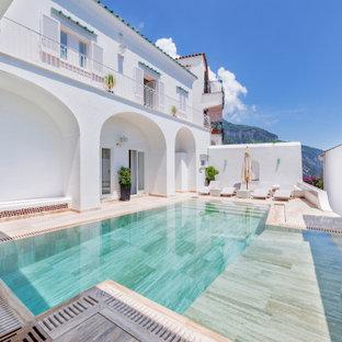 Ejemplo de piscina infinita, actual, grande, a medida, en patio, con privacidad y adoquines de piedra natural