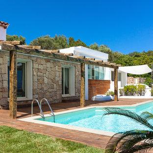 Immagine di una piscina mediterranea di medie dimensioni e dietro casa con pedane