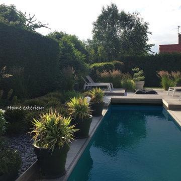 Abords d'une piscine avec plusieurs terrasses et massifs à Lesquin