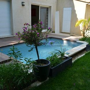 Bild på en liten funkis rektangulär pool framför huset, med trädäck