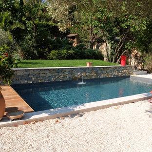Ejemplo de piscina contemporánea, de tamaño medio, rectangular, en patio delantero, con gravilla