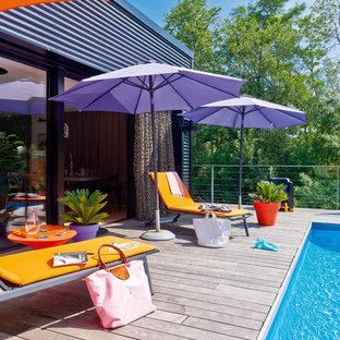 Cette image montre une piscine sur une terrasse en bois design de taille moyenne et rectangle.