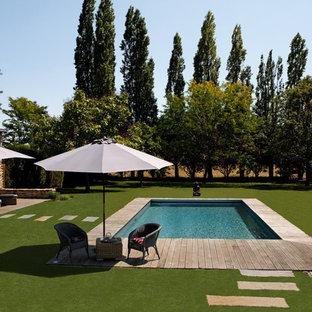 Ejemplo de piscina alargada, tradicional renovada, de tamaño medio, rectangular, en patio trasero, con entablado