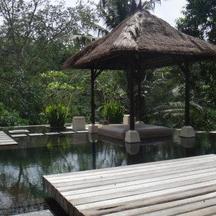 Idée de décoration pour une grande piscine sur une terrasse en bois arrière ethnique sur mesure.