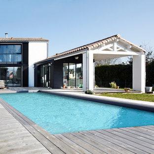 Inspiration pour une grande piscine sur une terrasse en bois arrière rustique rectangle.