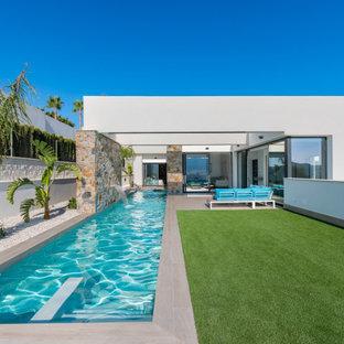 Ejemplo de piscina alargada, actual, grande, rectangular, en patio trasero