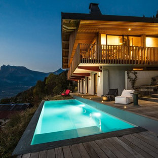 Inspiration for a rustic front yard rectangular pool remodel in Grenoble with decking
