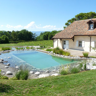 Exemple d'une grande piscine sur une terrasse en bois naturelle et arrière nature sur mesure.