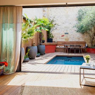 Ejemplo de piscina exótica, pequeña, en patio, con entablado