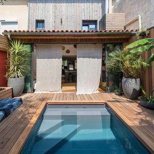 Réalisation d'une petit piscine sur une terrasse en bois méditerranéenne avec une cour.