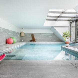 Idée de décoration pour une grand piscine intérieure design en L avec une dalle de béton.